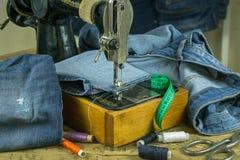 Rocznik szwalna maszyna z drelichem na drewnianym stole Obraz Royalty Free