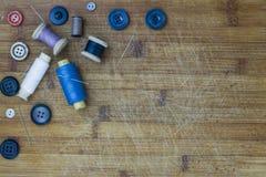 Rocznik szy narzędzia: różne colour cewy, igły, guziki Horyzontalny skład Drewniany tło układ z Zdjęcia Stock