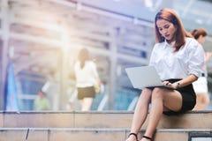 Rocznik tonował wizerunek młoda biznesowa kobieta używa laptop dla pracy przy outside biurem Internet rzeczy pojęcie fotografia stock