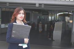 Rocznik tonował wizerunek atrakcyjna młoda Azjatycka biznesowa kobieta z ringowego segregatoru odprowadzeniem przy wejściem staci fotografia royalty free