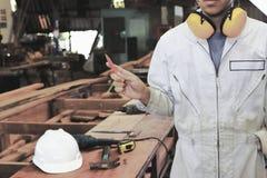 Rocznik tonujący wizerunek młody cieśla trzyma ołówek w rękach w drewnianym warsztatowym tle w białym bezpieczeństwo mundurze Prz zdjęcie royalty free
