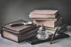Rocznik ustawiający z wygłupy rezerwuje, stary materiały, drewniany pióro, inkwell, magnifier na w górę biurka, Pojęcie czytanie  obraz stock