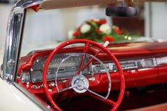 Rocznika ślubny samochód w czerwieni z panna młoda kwiatu bukietem Obrazy Stock