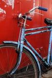 Rocznika błękitny bicykl na czerwonym tle Zdjęcie Stock