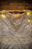 Rocznika bielu koronki szydełkowy wierzchołek na wieszaku z girlandą zaświeca na drewnianym tle Obrazy Royalty Free