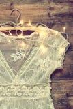 Rocznika bielu koronki szydełkowy wierzchołek na wieszaku z girlandą zaświeca na drewnianym tle Zdjęcie Royalty Free