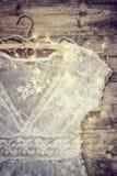 Rocznika bielu koronki szydełkowy wierzchołek na wieszaku z girlandą zaświeca na drewnianym tle Obraz Stock