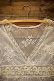 Rocznika bielu koronki szydełkowy wierzchołek z wieszakiem na drewnianym tle Fotografia Royalty Free