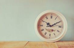 Rocznika bielu zegar na drewnianym tle zdjęcia stock