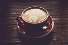 Rocznika brzmienie kawa w czerwonej filiżance na drewnianym rocznika stole obraz royalty free