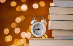 Rocznika budzik i stos książki obrazy stock