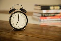 Rocznika budzik na nieociosanym drewno stole Przedstawienia 7 godzin stos Zdjęcia Stock