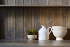 Rocznika crockery i mała roślina na ciemnym drewnianym tle Zdjęcie Stock