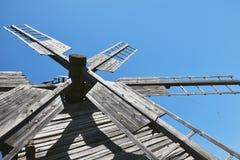 Rocznika drewniany wiatraczek żegluje nad jasnym niebieskim niebem Obrazy Royalty Free