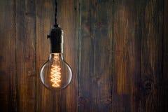 Rocznika Edison płonący typ żarówka na drewnianym tle Fotografia Royalty Free