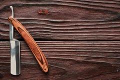 Rocznika fryzjera męskiego sklepu prostej żyletki narzędzie na drewnianym tle Obraz Royalty Free