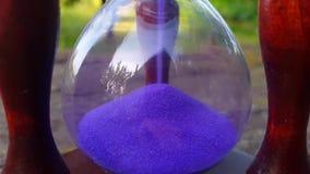 Rocznika hourglass z błękitnym piaska dolewaniem na natury tle zbiory