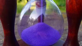 Rocznika hourglass z błękitnym piaska dolewaniem na natury tle zbiory wideo
