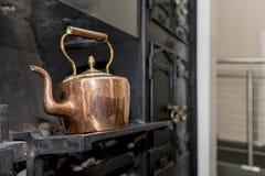Rocznika i antyka miedziany czajnik na Wiktoriańskiej kuchence w trad Fotografia Royalty Free