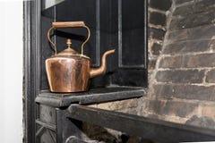 Rocznika i antyka miedziany czajnik na Wiktoriańskiej kuchence w trad Zdjęcia Royalty Free