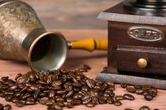 Rocznika kawowy ostrzarz, turka miedziany kawowy garnek i kawowe fasole na brown drewnianym tle, Obrazy Royalty Free