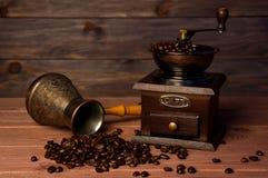 Rocznika kawowy ostrzarz, turka miedziany kawowy garnek i kawowe fasole na brown drewnianym tle, Fotografia Stock