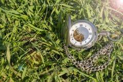 Rocznika kieszeniowego zegarka lying on the beach na zielonej trawie Steampunk zegarek dzie? sunny lato Zegarowy mechanizm jest s zdjęcia stock