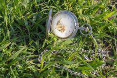 Rocznika kieszeniowy zegarek w m?skiej r?ce na tle zielona trawa Steampunk zegarek dzie? sunny lato Zegarowy mechanizm jest zdjęcia stock