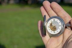 Rocznika kieszeniowy zegarek w m?skiej r?ce na tle zielona trawa Steampunk zegarek dzie? sunny lato zdjęcie stock