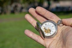 Rocznika kieszeniowy zegarek w m?skiej r?ce na tle zielona trawa Steampunk zegarek dzie? sunny lato obrazy stock