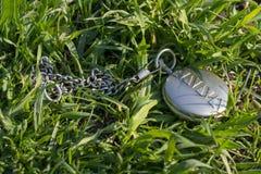 Rocznika kieszeniowy zegarek w zamkniętym formularzowym kłamstwie na zielonej trawie Zegarowy mechanizm no jest widoczny dzie? su fotografia stock
