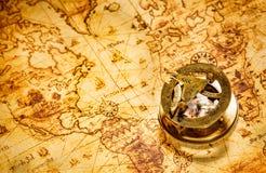 Rocznika kompas kłama na antycznej światowej mapie. Zdjęcia Royalty Free
