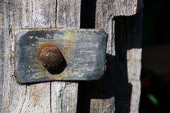 Rocznika kruszcowy element z ośniedziałym ryglem na tle szary drewniany drzwi w starej zaniechanej stajni fotografia royalty free