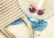 Rocznika lata s?omy pla?y ?ozinowa torba, s?o?c szk?a, kapelusz, przykrywki beachwear opakunek na piasku, tropikalny t?o obraz stock