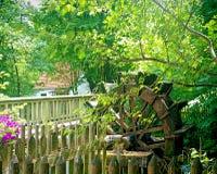 Rocznika młyńskiego koła wodny bieg blisko drewnianego mosta Fotografia Royalty Free