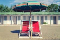 Rocznika plażowy krzesło, ubrella i buda, obraz royalty free