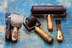 Rocznika projekta artysty narzędzia: czarni gumowi rolownika, dużych i małych kit noże na błękitnej farby drewnianym tle, diy nar Obraz Royalty Free