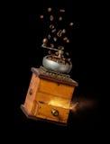 Rocznika ręczny kawowy ostrzarz z kawowymi fasolami i mlejącą kawą na czarnym tle Zdjęcie Stock
