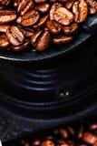 Rocznika ręczny kawowy ostrzarz z kawowymi fasolami na drewnianym brązie Zdjęcia Stock