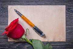 Rocznika rosebud fontanny papierowy czerwony pióro na drewnianej desce Obraz Stock