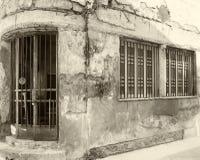 Rocznika sepiowy stary zaniechany handlowy dom na kącie z rozdrabnianie ścianami i rdzewieć stalowymi pręt przez okno i drzwi zdjęcia royalty free