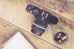 Rocznika SLR kamery ashtray gazeta na drewnianym stole Zdjęcie Stock