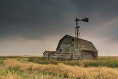 Rocznika stajnia, kosze i wiatraczek pod złowieszczymi ciemnymi niebami w Saskatchewan, Kanada obrazy royalty free