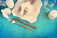 Rocznika stołowy położenie z storczykowymi dekoracjami, świeczki, wineglas Obrazy Stock