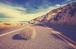 Rocznika stonowany tumbleweed na pustej drodze obraz stock