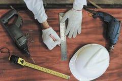 rocznika stonowany wizerunek Widok z lotu ptaka ręki pracuje na drewnianej desce z narzędzia tłem cieśla Pomiarowa taśma, zbawczy Obrazy Stock