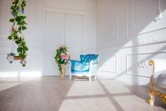 Rocznika stylu krzesło w klasycznym wewnętrznym pokoju z światłem słonecznym i kwiatami Fotografia Stock