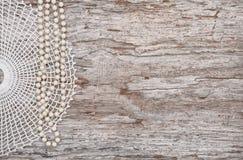 Rocznika tło z paciorkowatą kolią i koronką na starym drewnie Fotografia Stock