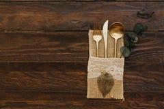 Rocznika złocisty cutlery z eukaliptusem stary drewniany tło zdjęcia stock