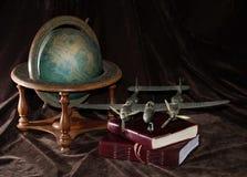 Rocznika Zabawkarski samolot z kulą ziemską i książkami fotografia royalty free